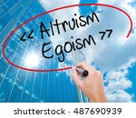 Small photo of Man Hand writing Altruism - Egoism with black marker on visual screen. Business, technology, internet concept. Modern business skyscrapers background. Stock Photo