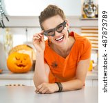 Small photo of Frightful Treats all the way. Portrait of smiling young woman in party bat glasses in the Halloween decorated kitchen