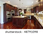 Stock photo kitchen in luxury home with cherry wood cabinetry 48791098