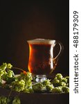 Small photo of Antique glass tankard filled with ale on a rustic barrel with hops