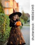 Small photo of Eve of All Saints' Day. Cute little girl portrays the evil enchantress. She is wearing a dark dress and a hat. In the hands of the girl Jack-o-lantern. Children adore Halloween.