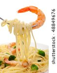A fork with linguine and shrimp on a white background, Focus on the shrimp - stock photo