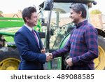 Small photo of Farmer And Businessman Shaking Hands With Tractor In Background