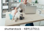 Stock photo young woman at home working at desk and cuddling her lovely cat pets and lifestyle concept 489137011
