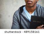 teenage boy holding a bible. | Shutterstock . vector #489158161