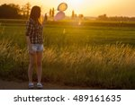 woman with balloons in sunset | Shutterstock . vector #489161635