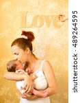 Mother Kissing Newborn Son At...