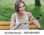beautiful girl eats salad in... | Shutterstock . vector #489484489