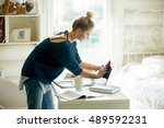 Stock photo side view portrait of young beautiful happy smiling casual woman wiping laptop screen doing 489592231