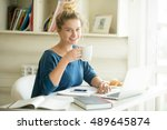 Stock photo portrait of young beautiful casual woman sitting at office desk enjoying her cup of coffee while 489645874
