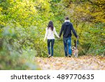 Stock photo young couple with dog on a walk in autumn forest 489770635