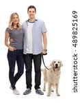 Stock photo full length portrait of a young couple posing with their dog isolated on white background 489825169