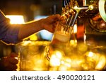 waiter pours beer into a mug | Shutterstock . vector #490020121