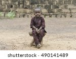 Small photo of Little African Boy Sitting Outdoors posing with a big Smile on his Face