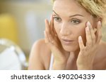 middle aged blond woman putting ... | Shutterstock . vector #490204339