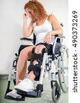 Small photo of Dejected woman with her knee in a brace and a post-operative scar sitting in a wheelchair with her head resting on her hand in a disability and health care concept