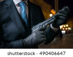 Hitman or assassin holds pistol with silencer in hands.