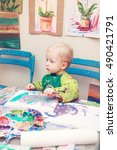 Small photo of Cute adorable little baby boy girl toddler sitting in art studio indoors and drawing painting with brushes, pencils, pastel. Early child development concept