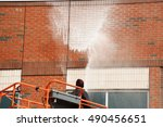 outdoor worker cleaning the exterior wall of building through pressure water - stock photo