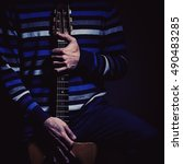 Small photo of Musician and his gypsy guitar in dark blue ambiance.