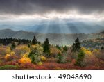 Blue Ridge Parkway Scenic Autumn Landscape with sunbeams over mountains w/ fall foliage - stock photo