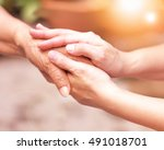 Small photo of Caregiver, carer hand holding elder hand in hospice care. Philanthropy kindness to disabled concept.