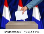 Small photo of Election in Netherlands. The hand of woman putting her vote in the ballot box. Dutch flags on background.