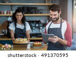 smiling waiter using digital... | Shutterstock . vector #491370595