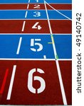Starting numbers on a red and blue striped athletic track - stock photo