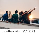 Small photo of Group of friends partying on terrace with drinks. Young men and women enjoying drinks on rooftop at sunset.