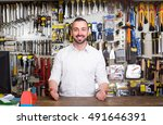 Small photo of portrait of young cheerful european man at the cash desk working in tool-ware shop