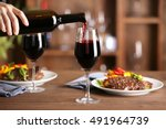 pouring red wine into glass at...   Shutterstock . vector #491964739