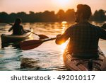 Meeting sunset on kayaks. Rear view of young couple kayaking on lake together with sunset in the backgrounds