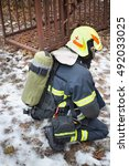 Small photo of MOSCOW - DEC 17, 2014: Firefighter wearing helmet with oxygen cylinder in North Eastern Administrative District (Russian Emergency Situations Ministry)