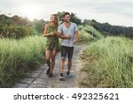 Stock photo outdoor shot of young couple in love walking on pathway through grass field man and woman walking 492325621