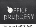 Small photo of office drudgery phrase handwritten on chalkboard with vintage precise stopwatch used instead of O