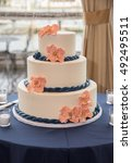Small photo of Three-Tier White Wedding Cake Decorated with Pink Fondant Flowers