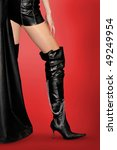 Sexy woman in leather outfit and black leather high stiletto boots Isolated silhouette on red background with clipping path - stock photo