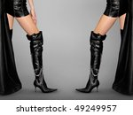 Sexy woman legs in black high stiletto boots Isolated on gray background - stock photo