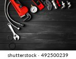 Plumber Tools On A Gray Wooden...