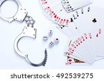 Small photo of Playing cards, dices, and handcuff on white background, gambling against the law concept