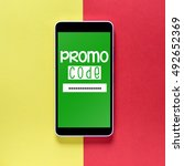 Small photo of Promo code. / Word promo code on the screen smartphone on a colored background