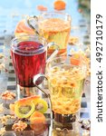 Small photo of Concept of herbal tea. Variety of herbal teas in glass mugs. Healthy caffein-free drinks with dried fruits. Chamomile, hibiscus and linden teas. Light airy caption. Grey background. Vertical