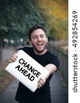 Small photo of Young man holding Change Ahead sign