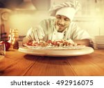 cook in kitchen with big wooden ... | Shutterstock . vector #492916075
