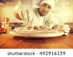 cook in kitchen with big wooden ... | Shutterstock . vector #492916159