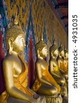 a row of seated buddha statues...