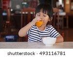 baby girl drinking orange juice  | Shutterstock . vector #493116781