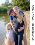 Small photo of Happy family with a pregnant mother being clasped from behind around her swollen belly by a loving husband watched by their little daughter alongside a lake