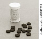 Small photo of Activated Charcoal Tablets For Cleansing The Body On A Gray Background Closeup. Black And White Photo